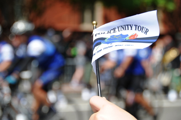 An observer waves a small flag during the arrival of participants in the Police Unity Tour at the National Law Enforcement Memorial in Washington, D.C., on May 12, 2018.