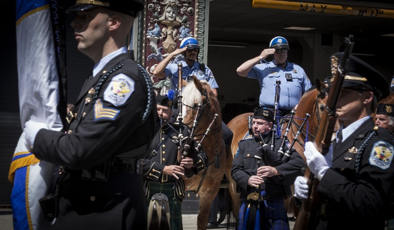 Law enforcement officers salute bagpipers during the the Blue Mass observation on May 7, 2018, an annual gathering to remember the contributions of those who have served in law enforcement and public safety agencies and to ask for continued protection for them in the future.
