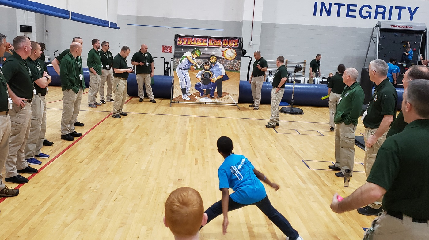 The child of a fallen officer pitches a baseball in the FBI Academy gymnasium in Quantico, Virginia, as National Academy students look on during a May 14, 2019 event organized by the National Academy and the non-profit Concerns of Police Survivors (C.O.P.S).