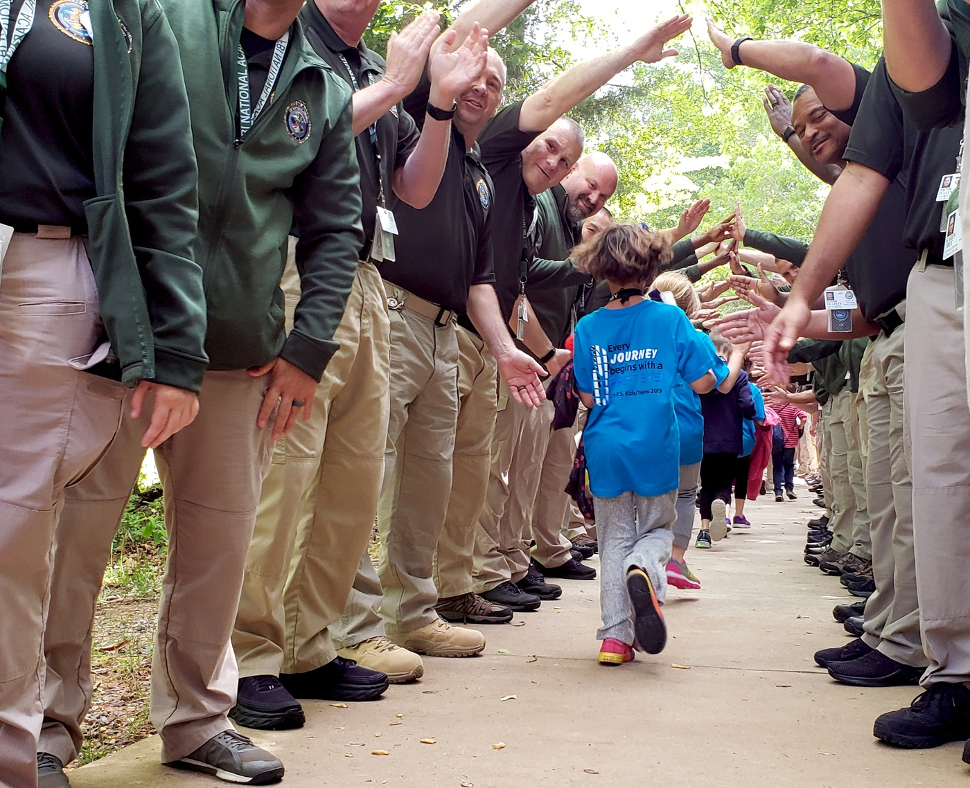 Children of fallen officers run through a tunnel composed of FBI National Academy Students at the FBI Academy in Quantico, Virginia, during a May 14, 2019 event organized by the National Academy and the non-profit Concerns of Police Survivors (C.O.P.S).