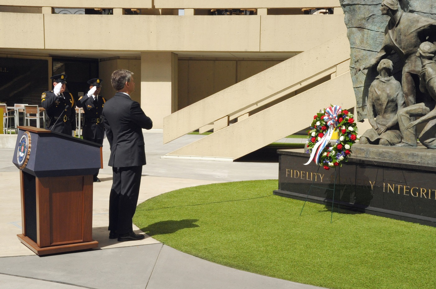 FBI Director Christopher Wray faces a wreath placed in honor of fallen special agents at a May 14, 2019 ceremony at FBI Headquarters in Washington, D.C., during National Police Week.