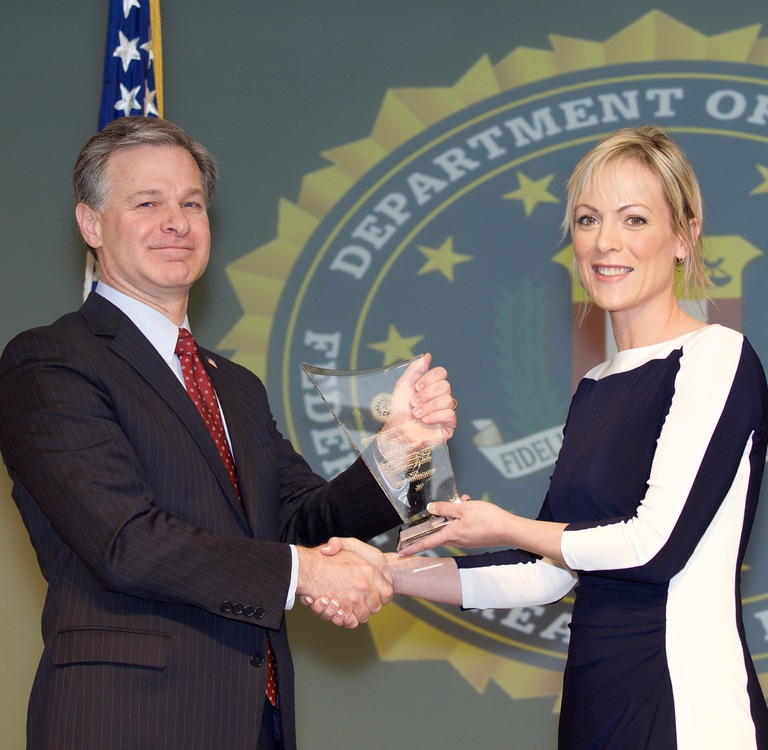 FBI Director Christopher Wray presents Portland Division recipient Safety Compass (represented by Esther Nelson) with the Director's Community Leadership Award (DCLA) at a ceremony at FBI Headquarters on April 20, 2018.
