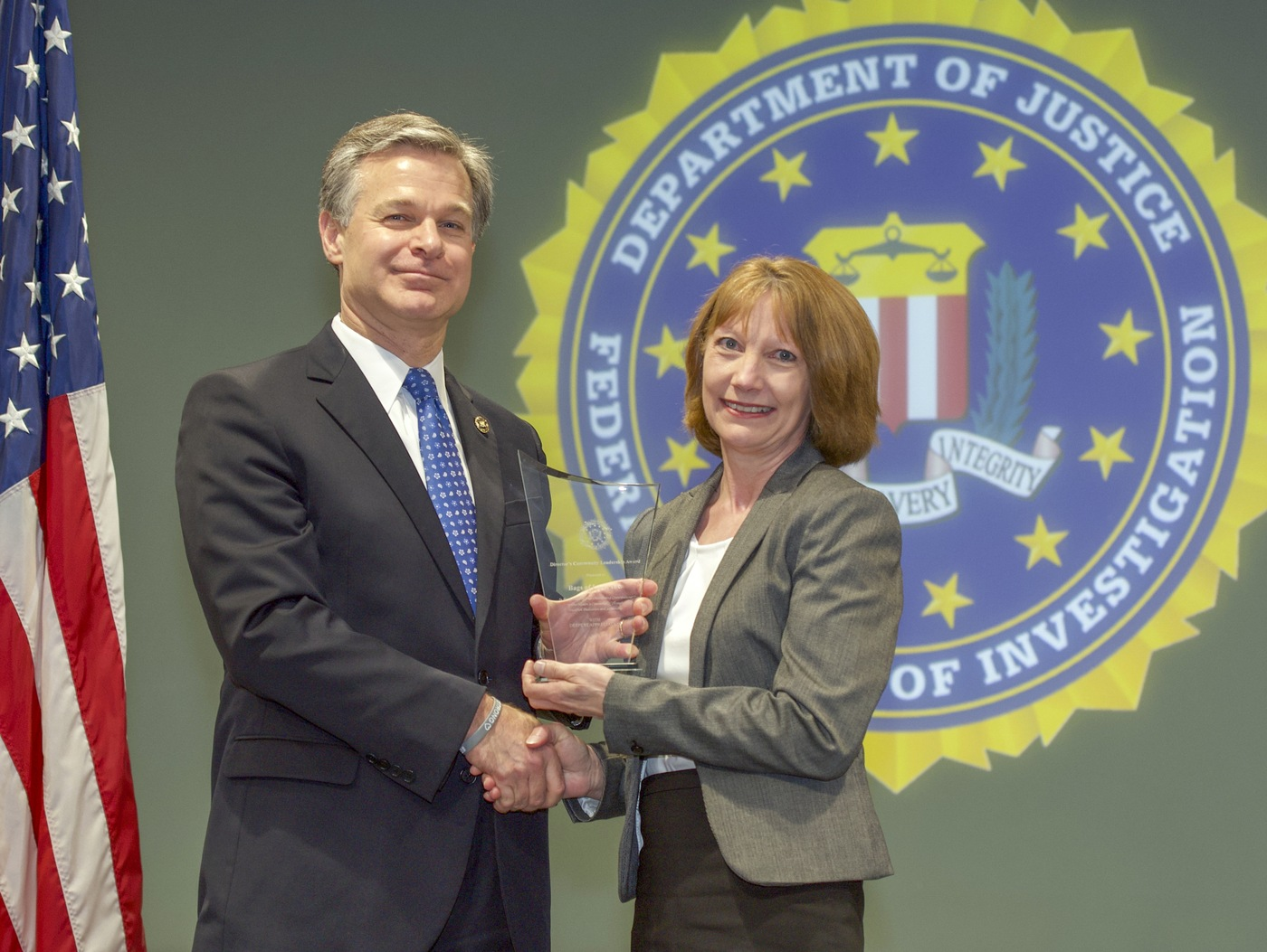 FBI Director Christopher Wray presents Portland Division recipient Bags of Love, Inc. (represented by Becky Stenzel) with the Director's Community Leadership Award (DCLA) at a ceremony at FBI Headquarters on May 3, 2019.