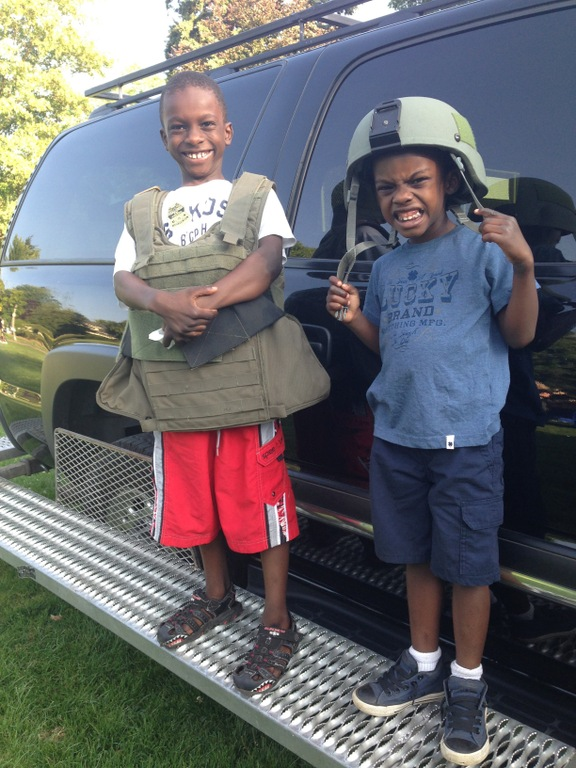 Two children wearing FBI gear near a Bureau vehicle at a National Night Out event on August 5, 2014 attended by FBI Portland.