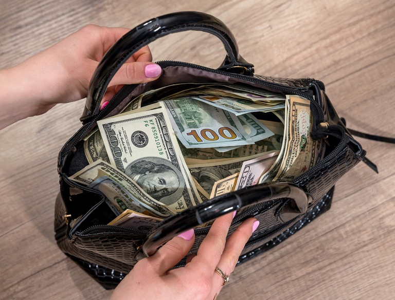 Stock image depicting woman holding open purse filled with currency.