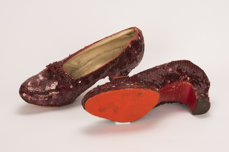 Ruby slippers worn by Judy Garland in the Wizard of Oz; one shoe is turned on its side and shows red felt on the bottom. The shoes were stolen in 2005 and recovered by the FBI in 2018.