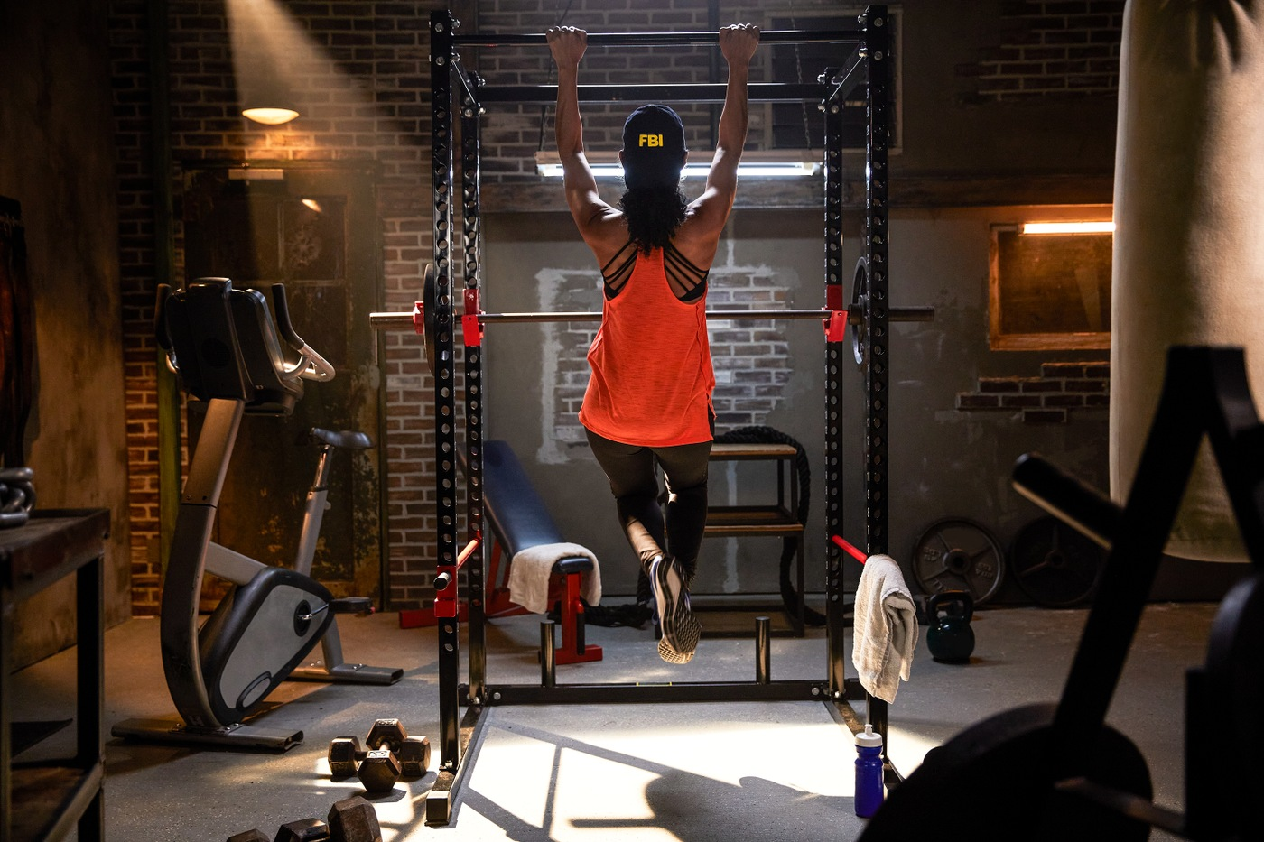 An FBI agent does a pull-up in the gym.