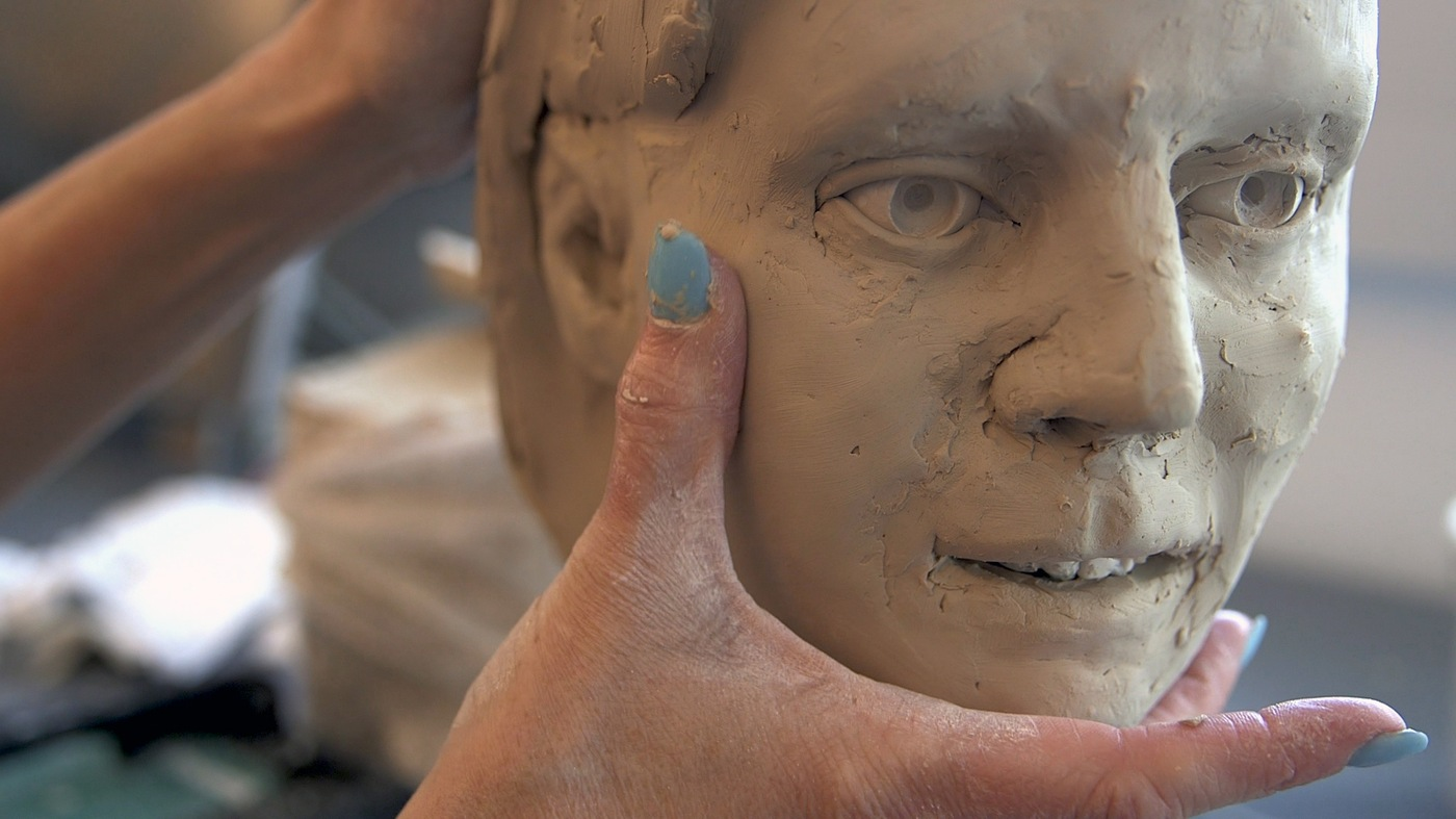 A forensic artist at the FBI Laboratory creates a facial approximation of an unidentified individual.