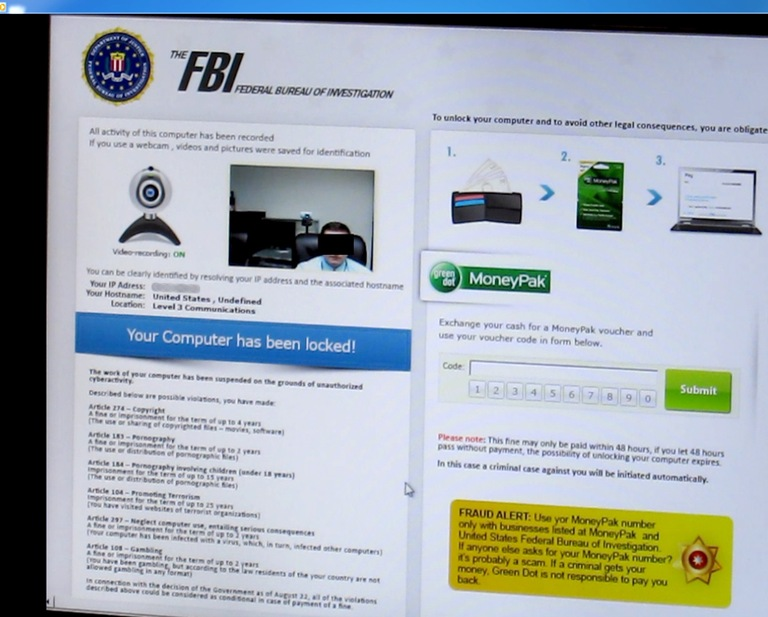 Computer monitor displaying the Reveton ransomware lock screen with the FBI logo and instructions on how to pay the ransom.
