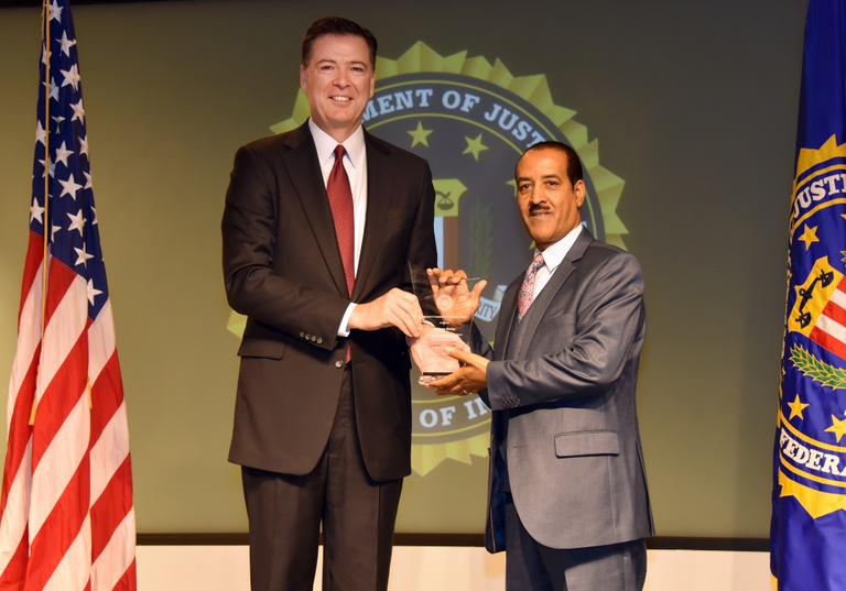 FBI Director James Comey presents Richmond Division recipient Seyoum Berhe with the Director's Community Leadership Award (DCLA) at a ceremony at FBI Headquarters on April 28, 2017.