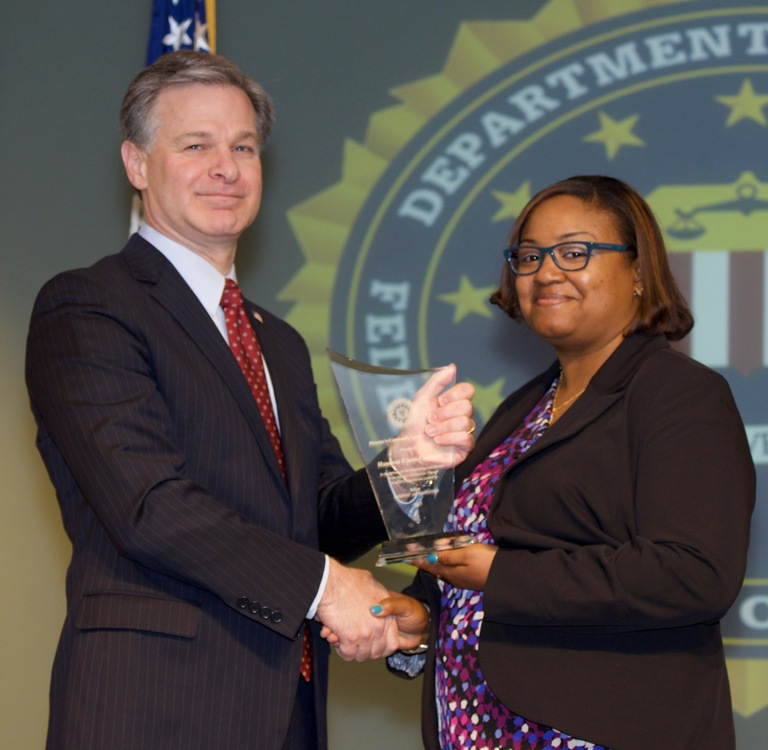 FBI Director Christopher Wray presents Richmond Division recipient the Hanover Cares Coalition (represented by Octavia Marsh) with the Director's Community Leadership Award (DCLA) at a ceremony at FBI Headquarters on April 20, 2018.