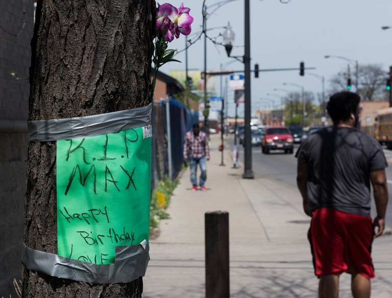 "Flowers and a sign that says, ""R.I.P. Max, Happy Birthday,"" is taped to a tree marking the spot where an individual was killed in Chicago."