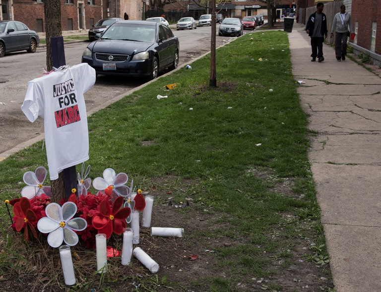 "Flowers, candles, and a t-shirt that says ""Justice for Marc"" mark the spot where an individual was killed in Chicago."