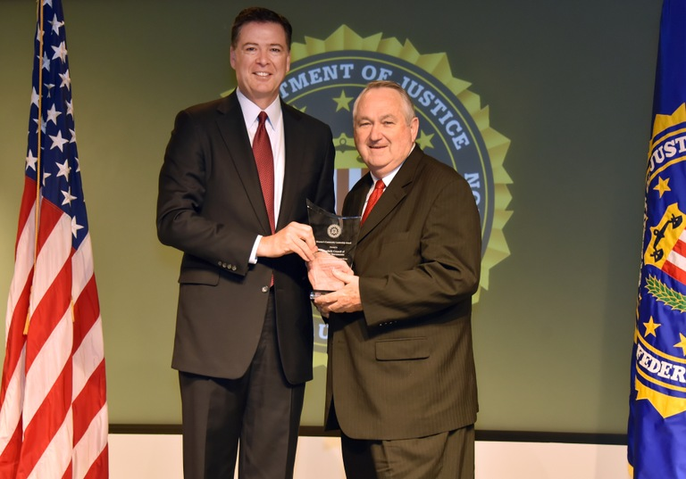 FBI Director James Comey presents Sacramento Division recipient the Interfaith Council of Greater Sacramento (represented by Jon Fish) with the Director's Community Leadership Award (DCLA) at a ceremony at FBI Headquarters on April 28, 2017.