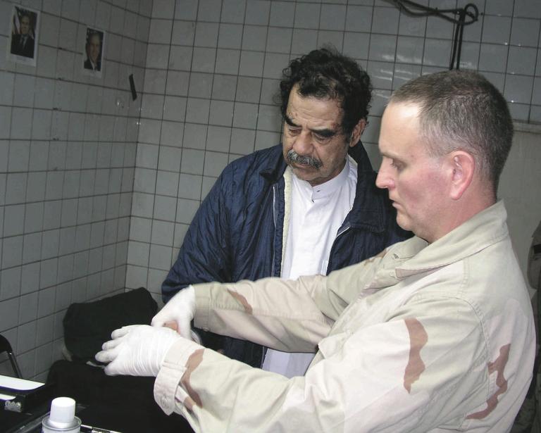 FBI Agent Fingerprints Saddam Hussein After Capture
