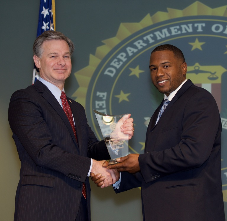FBI Director Christopher Wray presents San Antonio Division recipient Group Violence Intervention (represented by Martin Henderson) with the Director's Community Leadership Award (DCLA) at a ceremony at FBI Headquarters on April 20, 2018.