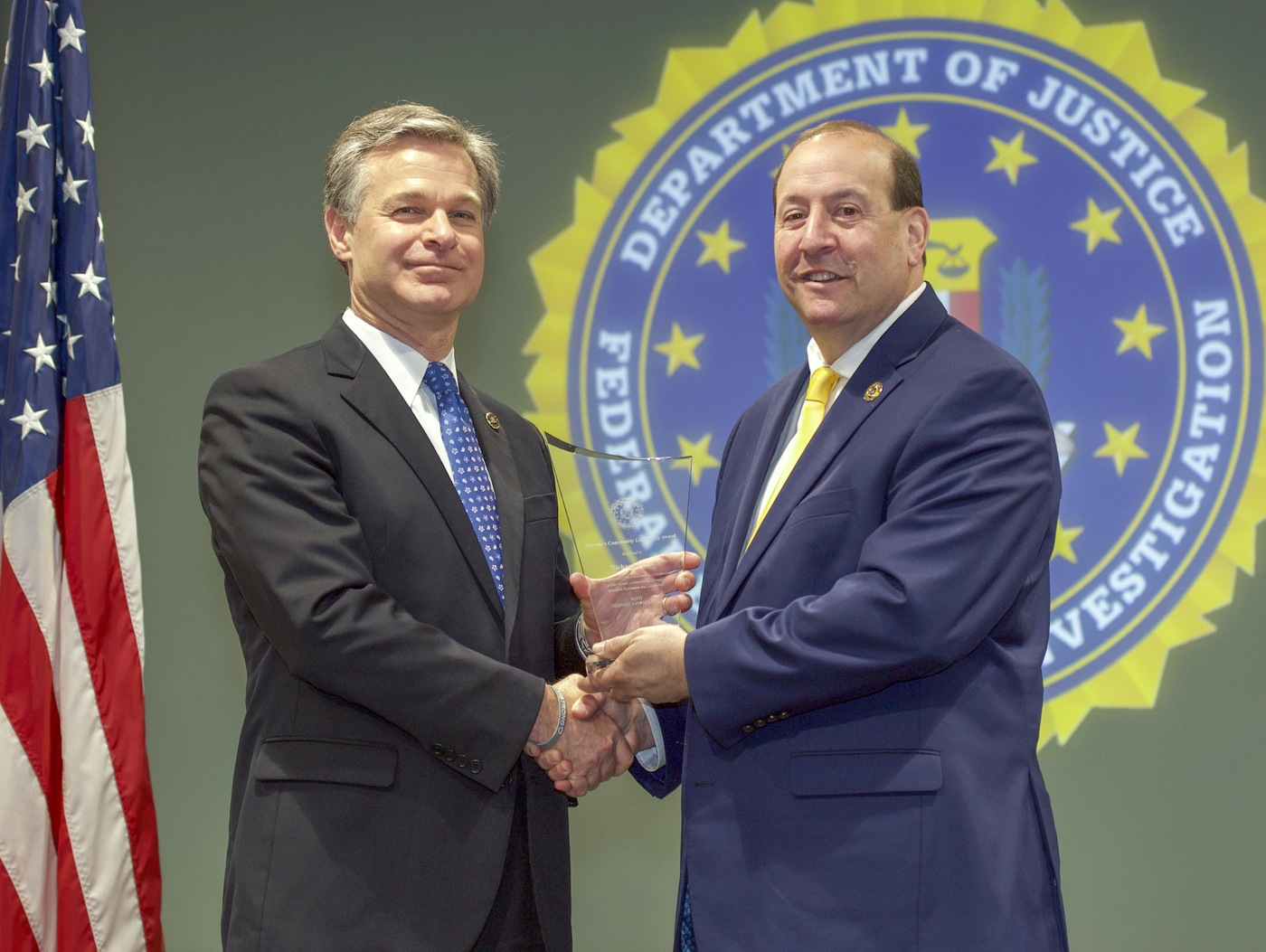 FBI Director Christopher Wray presents San Antonio Division recipient Richard Miller with the Director's Community Leadership Award (DCLA) at a ceremony at FBI Headquarters on May 3, 2019.