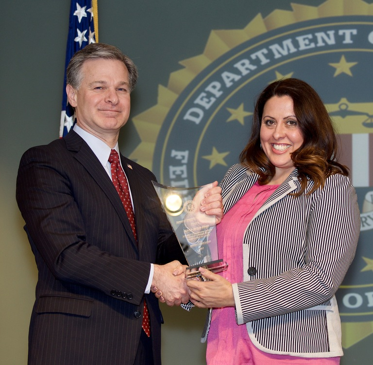 FBI Director Christopher Wray presents San Diego Division recipient MANA de San Diego (represented by Venus Molina) with the Director's Community Leadership Award (DCLA) at a ceremony at FBI Headquarters on April 20, 2018.