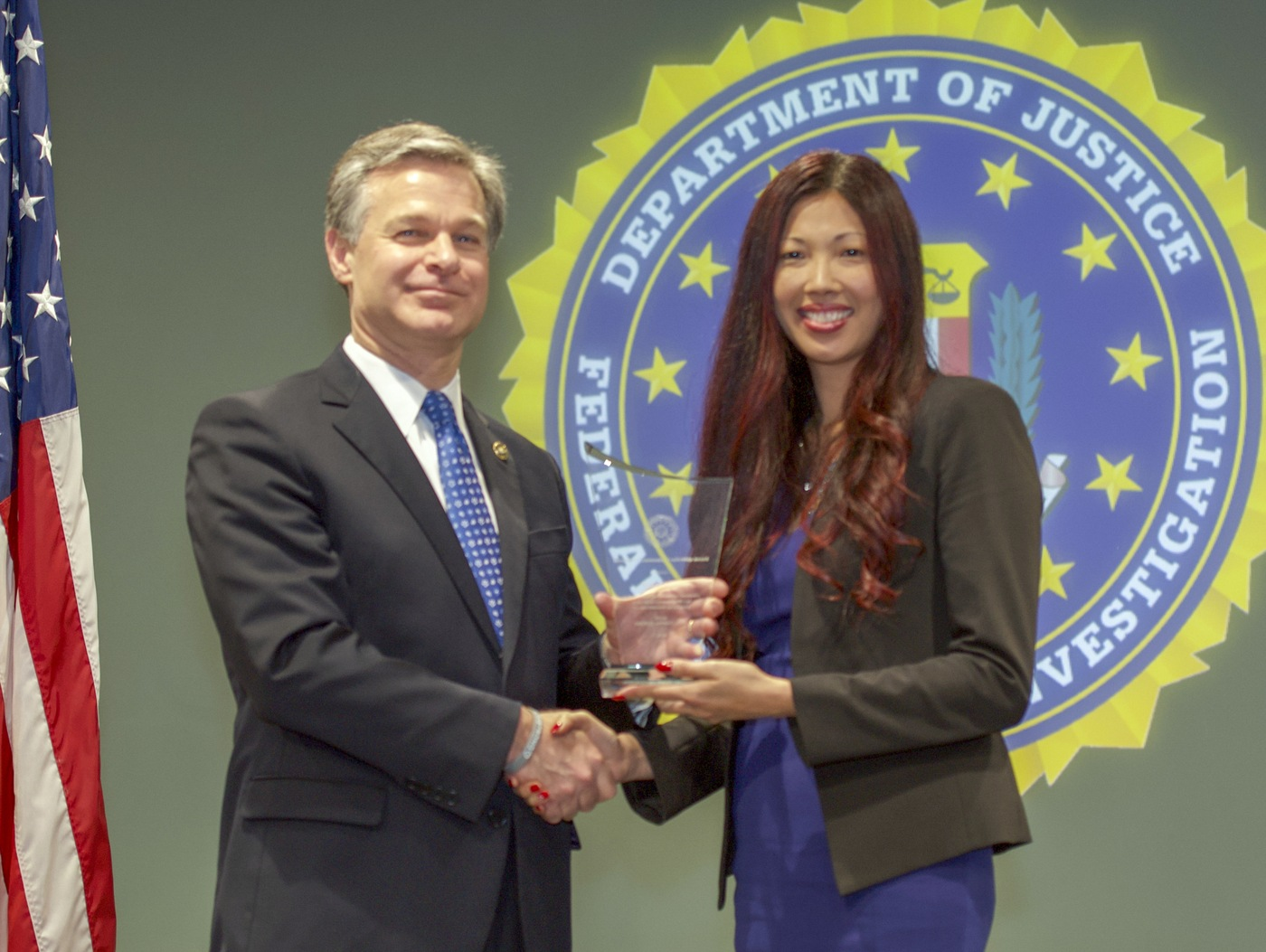 FBI Director Christopher Wray presents San Diego Division recipient Sandy Moul with the Director's Community Leadership Award (DCLA) at a ceremony at FBI Headquarters on May 3, 2019.
