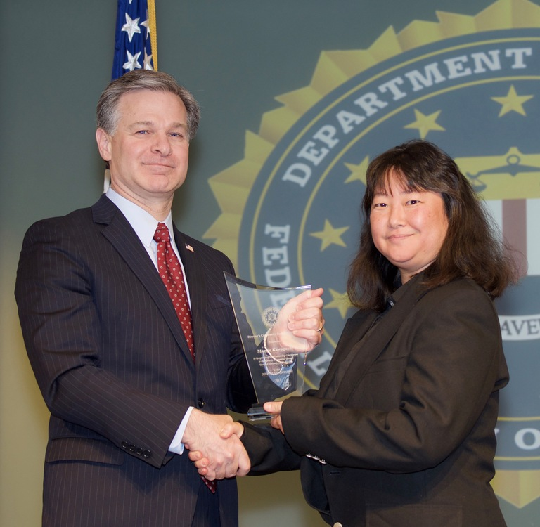 FBI Director Christopher Wray presents San Francisco Division recipient Mariko Kawaguchi with the Director's Community Leadership Award (DCLA) at a ceremony at FBI Headquarters on April 20, 2018.