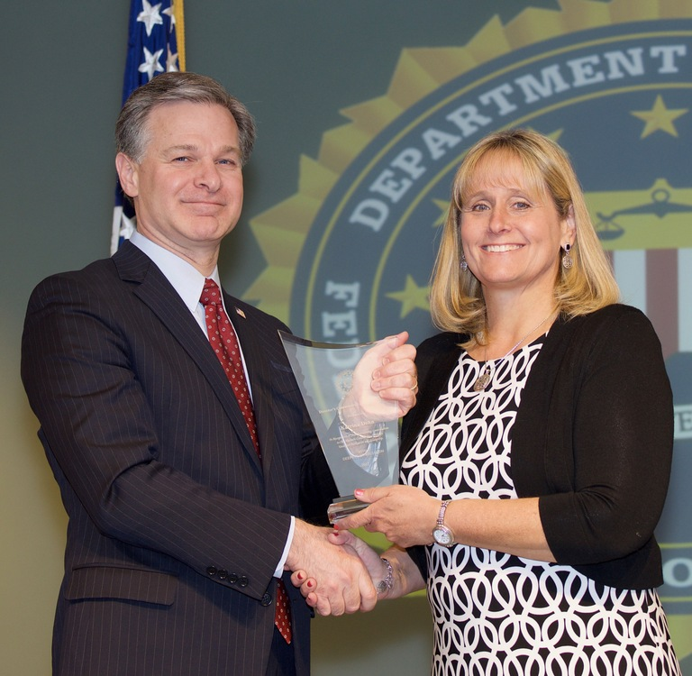FBI Director Christopher Wray presents Seattle Division recipient Katrina Dohn with the Director's Community Leadership Award (DCLA) at a ceremony at FBI Headquarters on April 20, 2018.