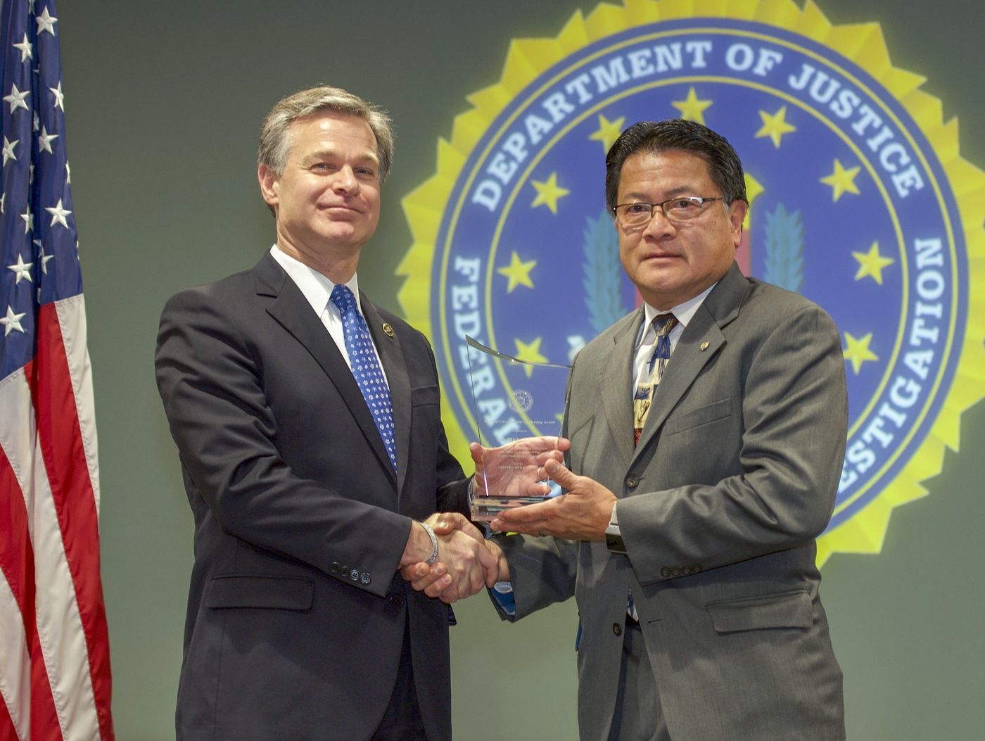 FBI Director Christopher Wray presents Seattle Division recipient Son Michael Pham with the Director's Community Leadership Award (DCLA) at a ceremony at FBI Headquarters on May 3, 2019.