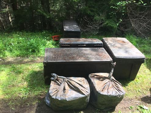 Cache of criminal accessories and stolen goods hidden by bank robber Bradley Steven Robinett in the Olympic National Forest and located by investigators on May 22, 2015.
