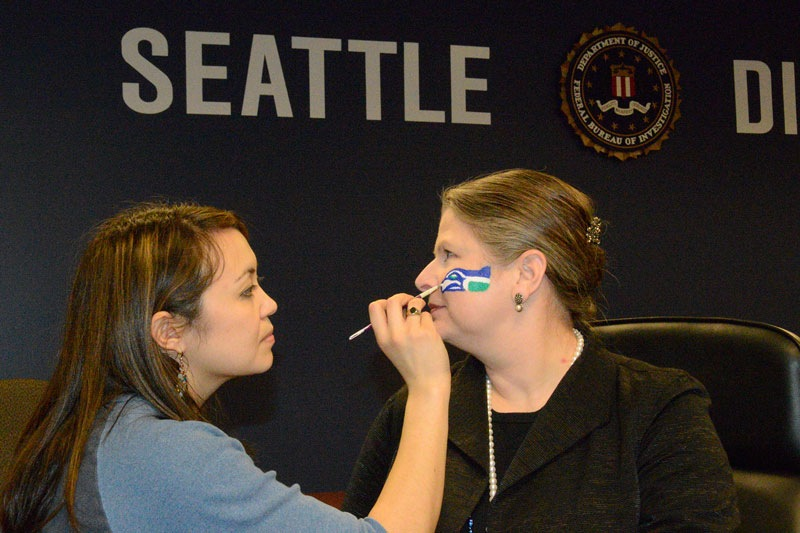 Special Agent in Charge Laura M. Laughlin gets her face painted in support of the Seattle Seahawks.