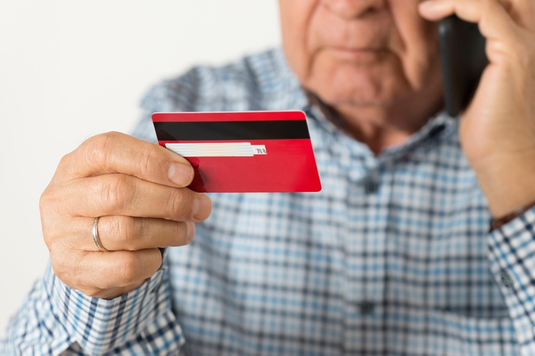 Stock image depicting a senior citizen on the phone and holding a credit card.