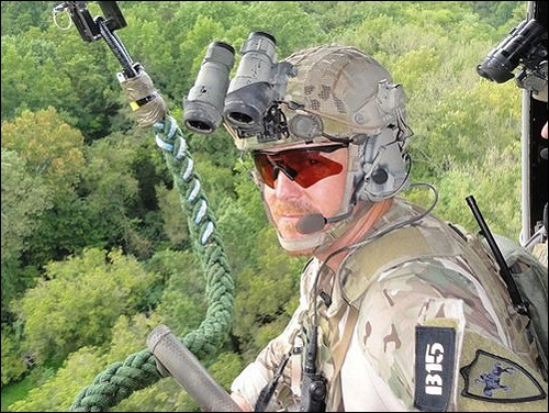 FBI agent wearing amber colored tactical glasses and kevlar helmet with binoculars.