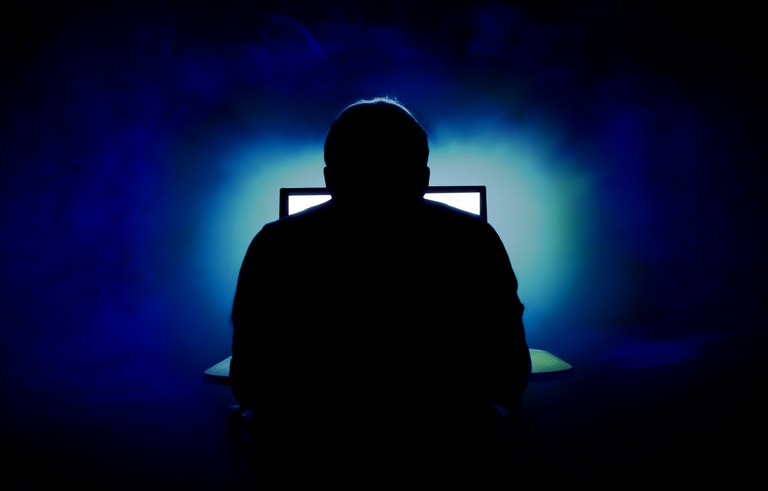 Stock image depicting silhouette of a man facing a computer with back to viewer.