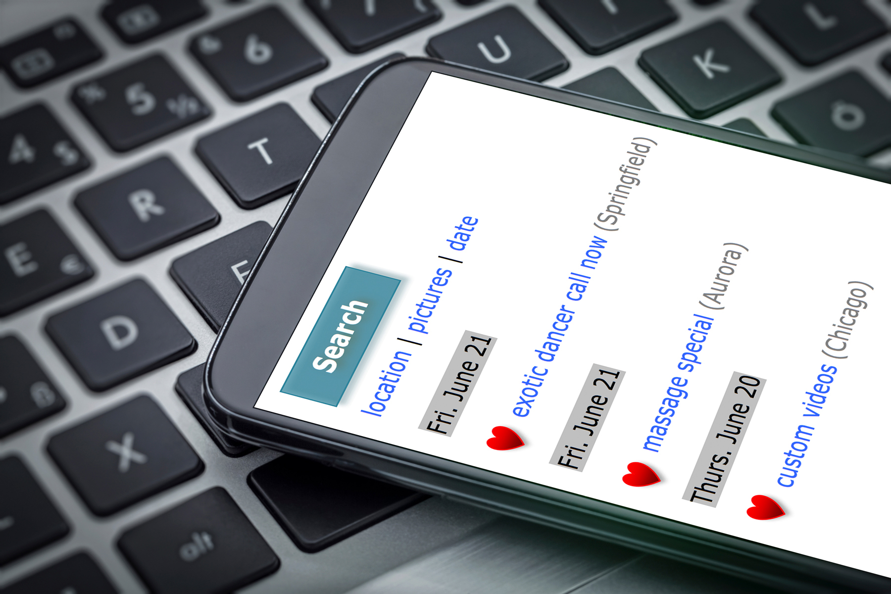 Stock image depicting a smartphone displaying a listing of online ads; the phone is laying atop a laptop keyboard.