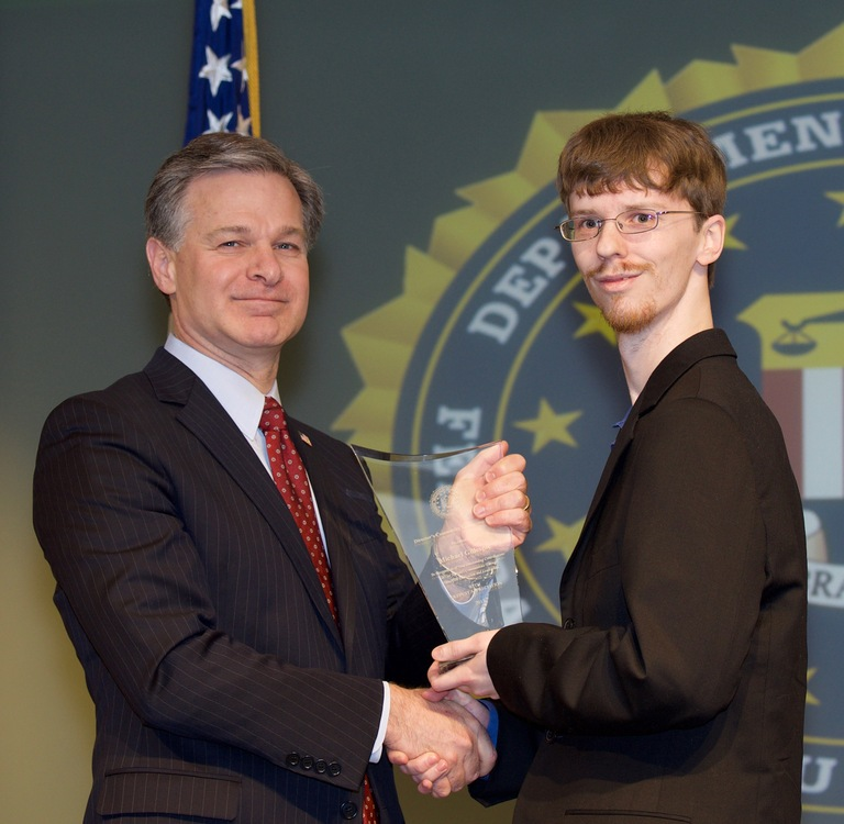 FBI Director Christopher Wray presents Springfield Division recipient Michael Gillespie with the Director's Community Leadership Award (DCLA) at a ceremony at FBI Headquarters on April 20, 2018.