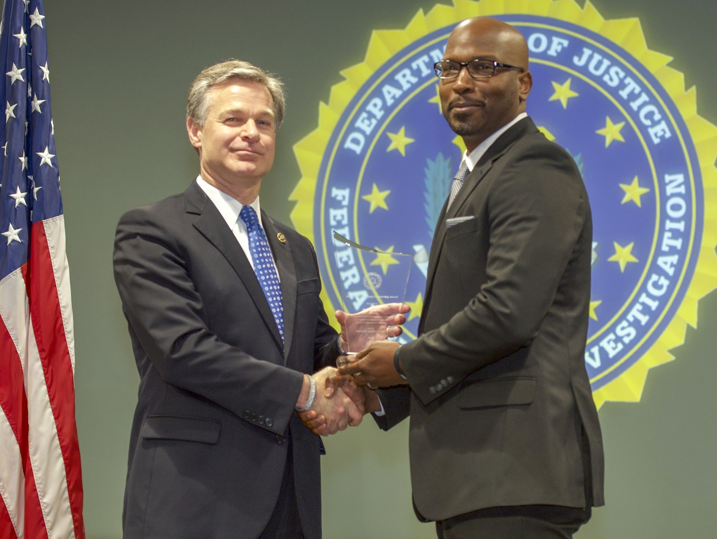 FBI Director Christopher Wray presents Springfield Division recipient The Outlet (represented by Michael Phelon) with the Director's Community Leadership Award (DCLA) at a ceremony at FBI Headquarters on May 3, 2019.