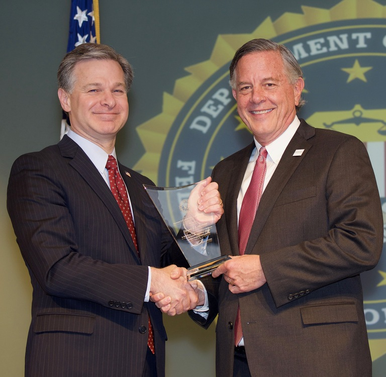 FBI Director Christopher Wray presents St. Louis Division recipient Daniel J. Ludeman with the Director's Community Leadership Award (DCLA) at a ceremony at FBI Headquarters on April 20, 2018.