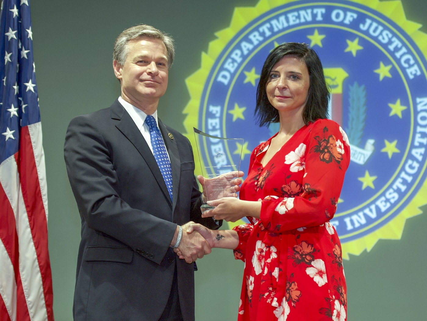FBI Director Christopher Wray presents St. Louis Division recipient the National Council on Alcoholism and Drug Abuse – St. Louis (represented by Nichole Dawsey) with the Director's Community Leadership Award (DCLA) at a ceremony at FBI Headquarters on May 3, 2019.