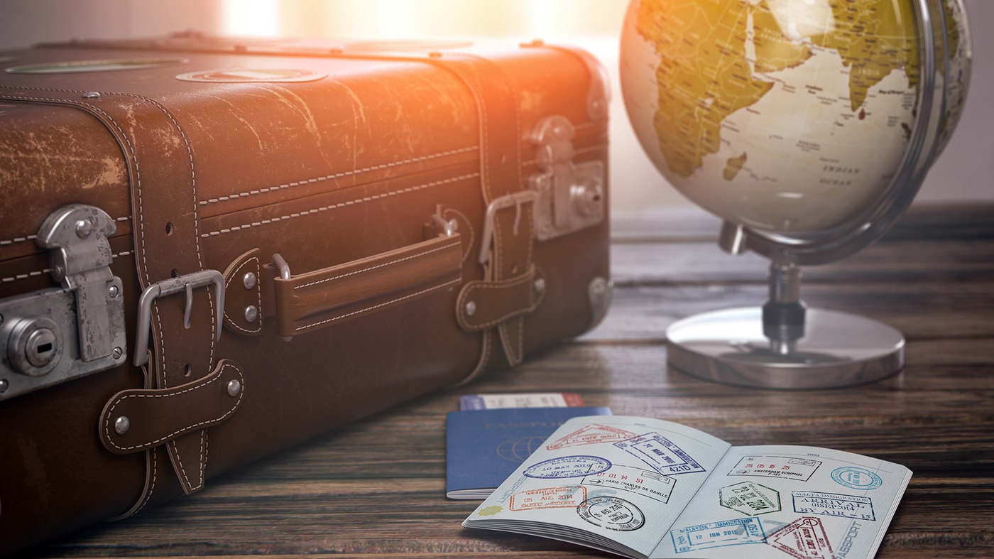 Stock image depicting a leather suitcase, globe, and open passport with multiple stamps.