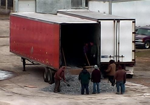 Surveillance photo showing members of Michael Wymer's Ohio chop shop ring emptying the scrap aluminum cargo out of a stolen trailer so the vehicle could be chopped up and sold as scrap metal.