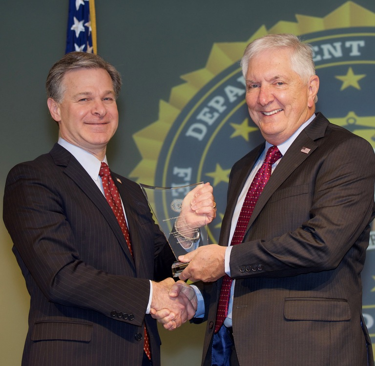 FBI Director Christopher Wray presents Tampa Division recipient Jack Harris with the Director's Community Leadership Award (DCLA) at a ceremony at FBI Headquarters on April 20, 2018.