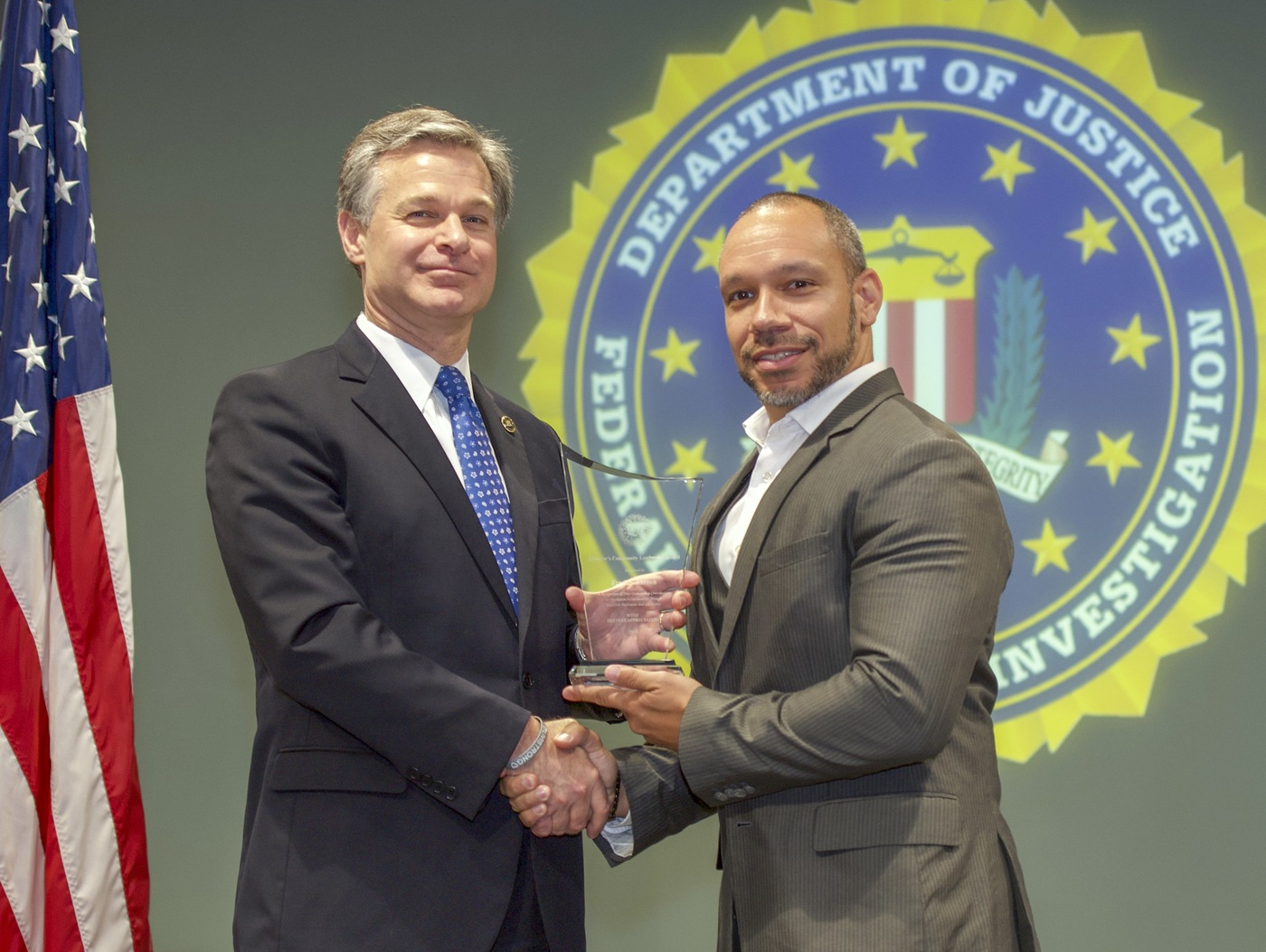 FBI Director Christopher Wray presents Tampa Division recipient Freddy Barton with the Director's Community Leadership Award (DCLA) at a ceremony at FBI Headquarters on May 3, 2019.