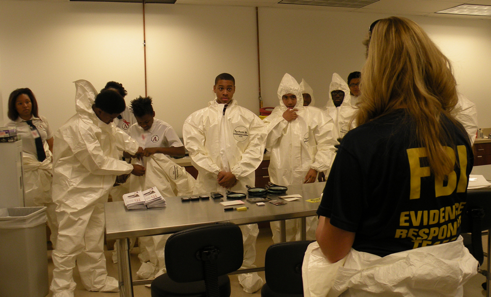 A member of the FBI Las Vegas Evidence Response Team instructs participants in the 2014 Teen Academy on evidence collection techniques.