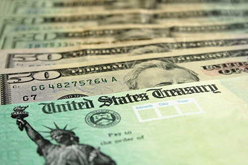 Treasury check and cash in stock photo.