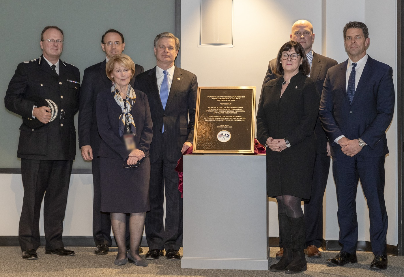 Kathryn Turman and FBI Director Christopher Wray presided over the installation at FBI Headquarters in December 2018 of a plaque marking the 30-year anniversary of the bombing of Pan Am Flight 103 over Lockerbie, Scotland. Also seen are (from left) Police Scotland Deputy Chief Constable Johnny Gwynne, Deputy Attorney General Rod Rosenstein, Allison di Rollo, Solicitor General of Scotland, Acting Attorney General Matthew Whitaker, and FBI Deputy Director David Bowdich.