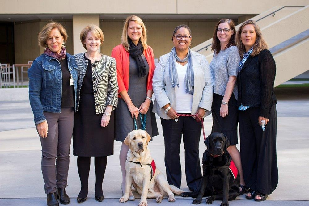 Kathryn Turman at FBI headquarters with (from left) Linda Milanesi, executive director of Assistance Dogs of the West, victim specialists  Staci Beers, Melony Tiddle, Karen Joyce-McMahon, and Jill Felice, founder of Assistance Dogs of the West. In the front row are FBI crisis response canines Wally and Gio.
