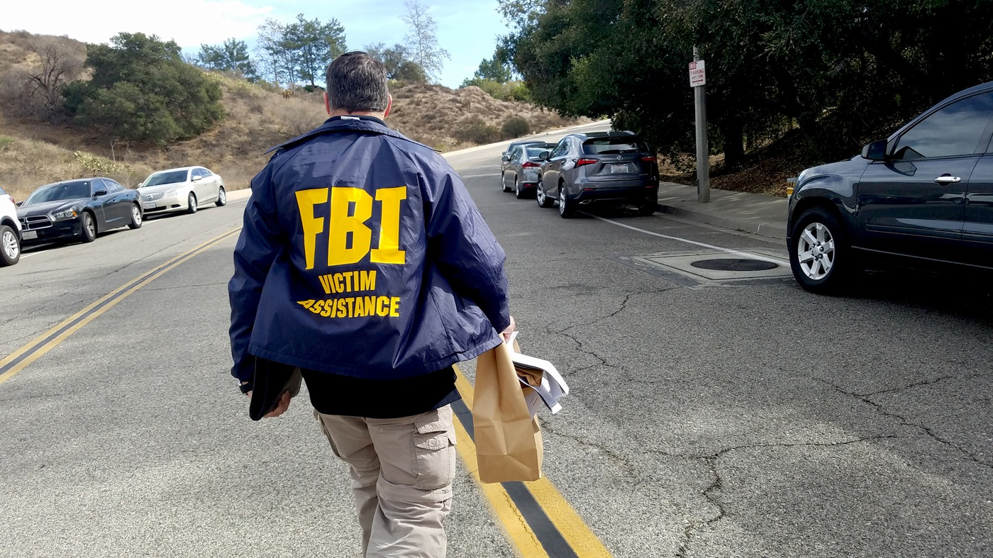 A Victim Services Response Team member carries a bag of personal effects from the incident site of a mass shooting in Thousand Oaks, California in November 2018.