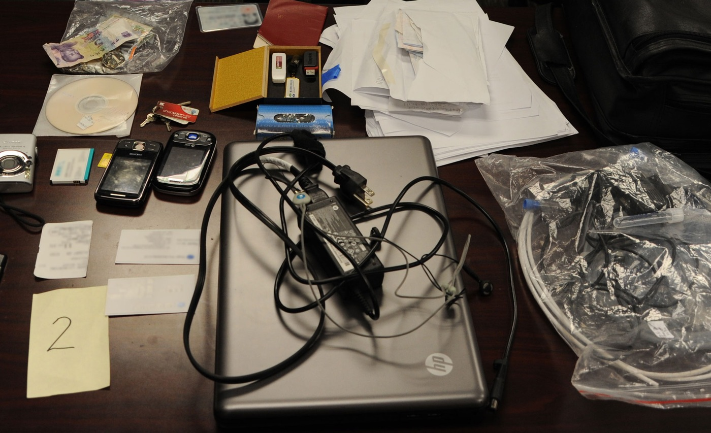 Evidence photo from Wenfeng Lu theft of trade secrets case depicting a variety of evidence items, including a laptop, receipts, business cards, cell phones, keys, and cords.