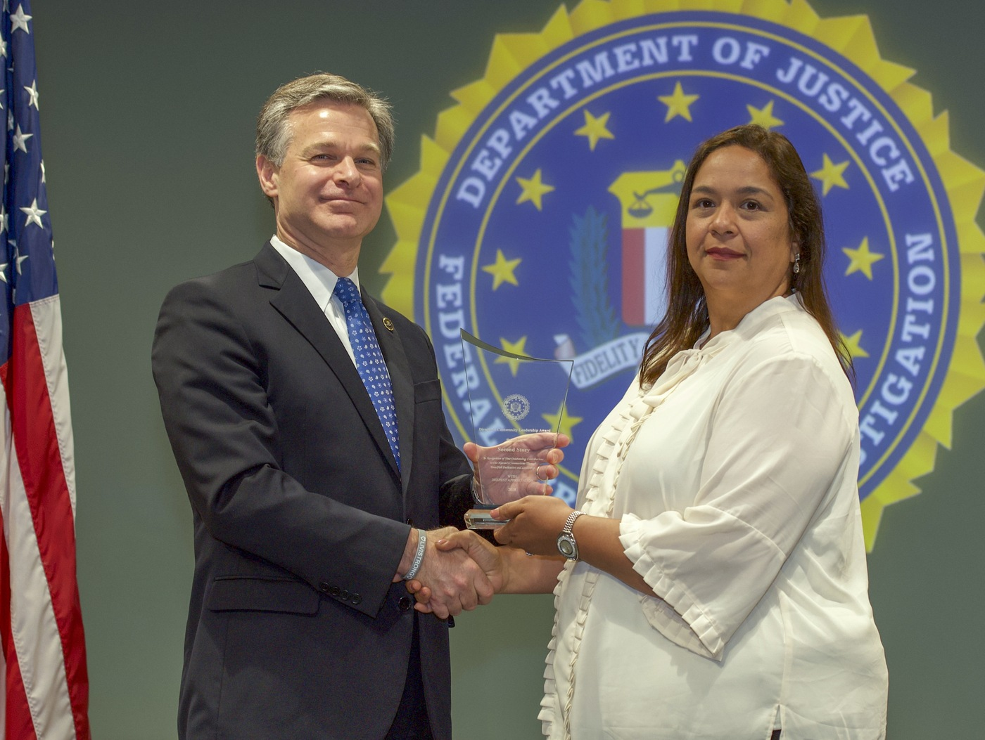 FBI Director Christopher Wray presents Washington Field Office Division recipient Second Story (represented by Nandred Navarro) with the Director's Community Leadership Award (DCLA) at a ceremony at FBI Headquarters on May 3, 2019.