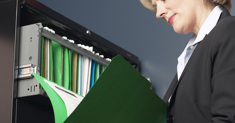 Stock image of woman holding file folder, standing at filing cabinet with open drawer. (From CJIS Link article)