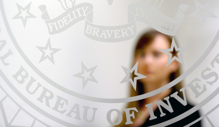 Woman Behind Glass Door Bearing FBI Seal