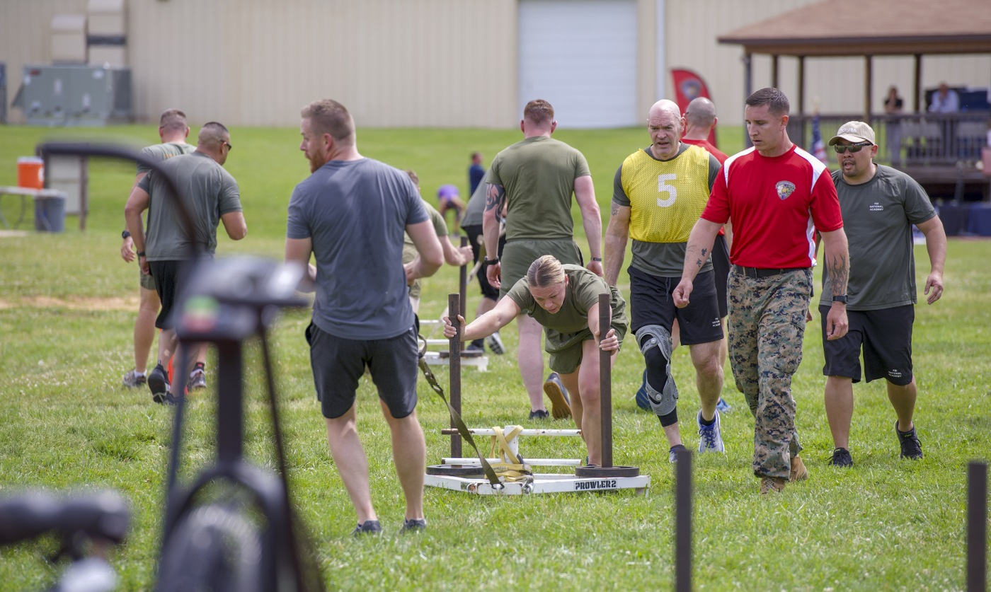 FBI, FBI National Academy, and Marine Corps participants move weighted sleds during a May 22, 2019 training and networking event with the Marine Corps Wounded Warrior Regiment at the FBI Academy in Quantico, Virginia.